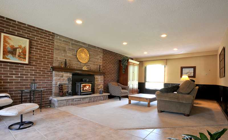 Family room has a combination of new ceramic and broadloom, a wood-burning insert, pot lighting, wainscoting and walk-out to the deck and pool area
