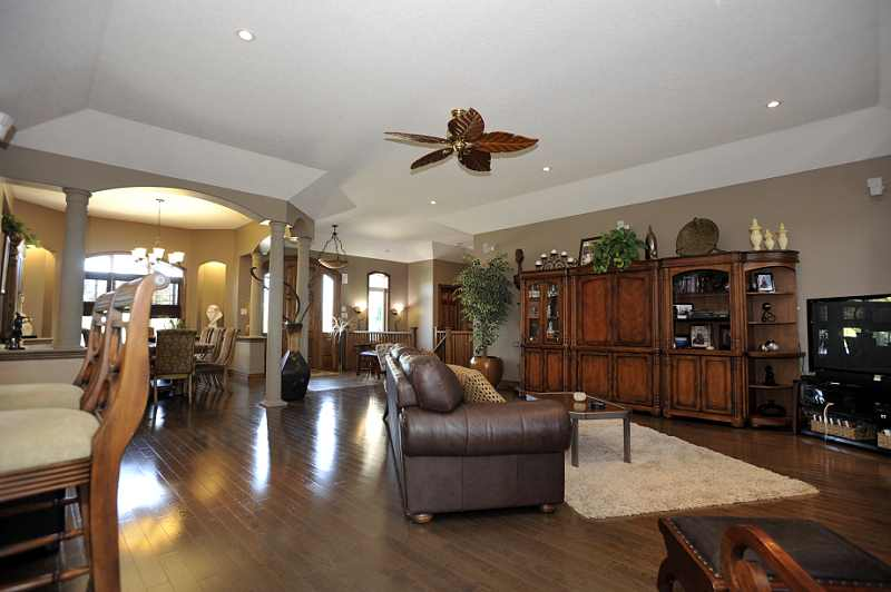 hardwood flooring, pot lighting, coffered ceilings, a gas fireplace