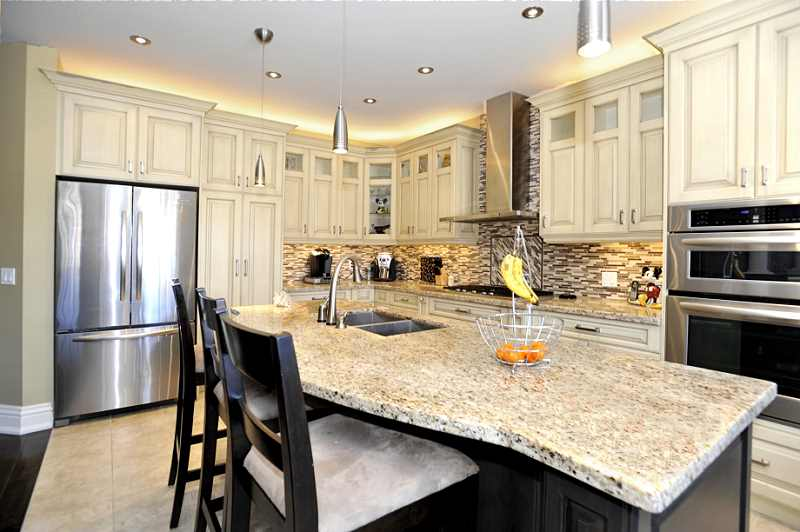huge centre island with breakfast bar pot lights granite counters