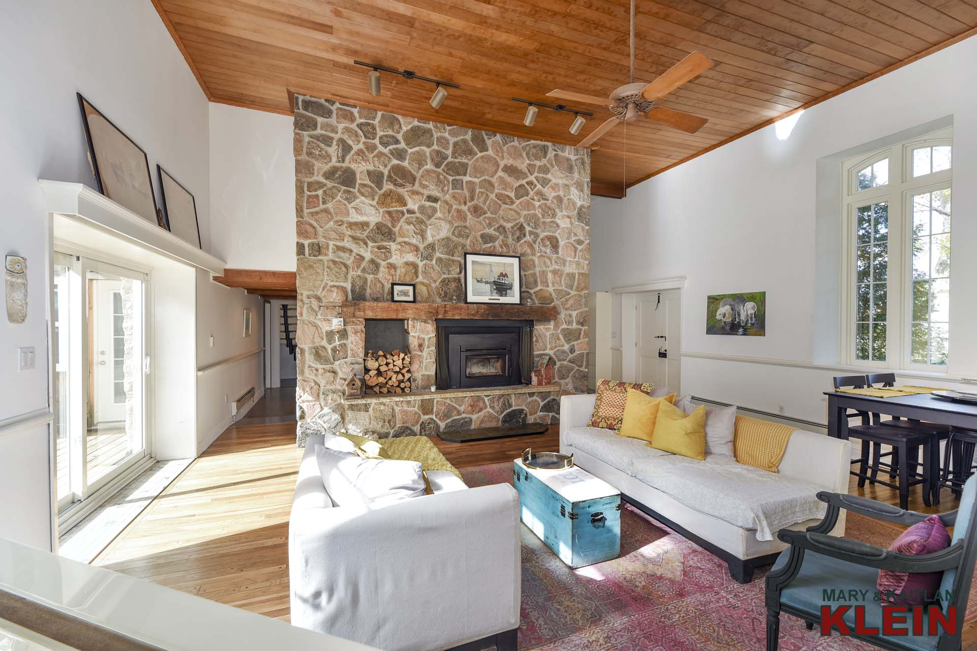 floor-to-ceiling stone wood burning fireplace with wooden mantel